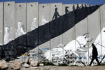 A Palestinian man walks past graffiti painted on Israel's controversial separation barrier in the Aida refugee camp situated inside the West Bank town of Bethlehem, on February 12, 2016. / AFP PHOTO / THOMAS COEX